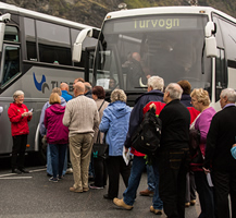 Guide welcoming passengers by the bus at the pier in Flam. By Terje Nesthus.